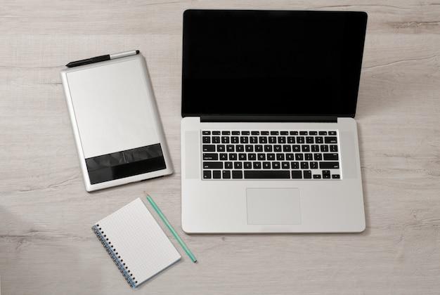 Abra el portátil, la tableta gráfica y el cuaderno con un lápiz sobre una mesa de luz, vista superior