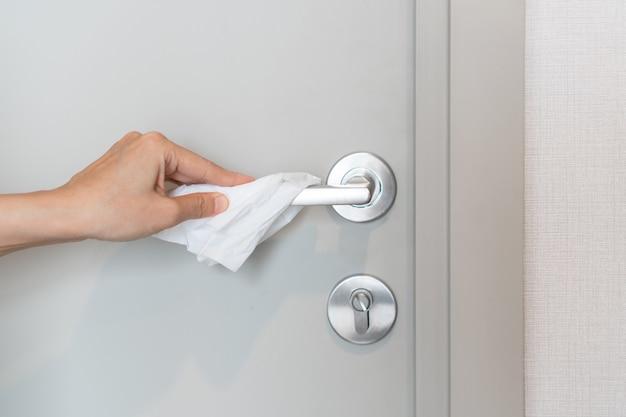 Abra la puerta con la mano con papel de seda para evitar el contacto directo de covid 19 y la prevención de gérmenes.