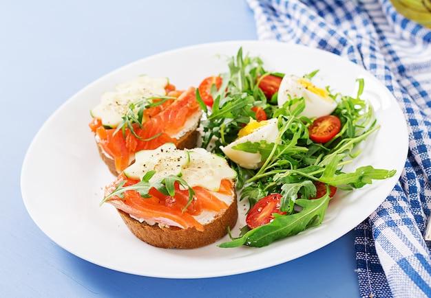 Abra los sándwiches con salmón, queso crema y pan de centeno en un plato blanco y ensalada