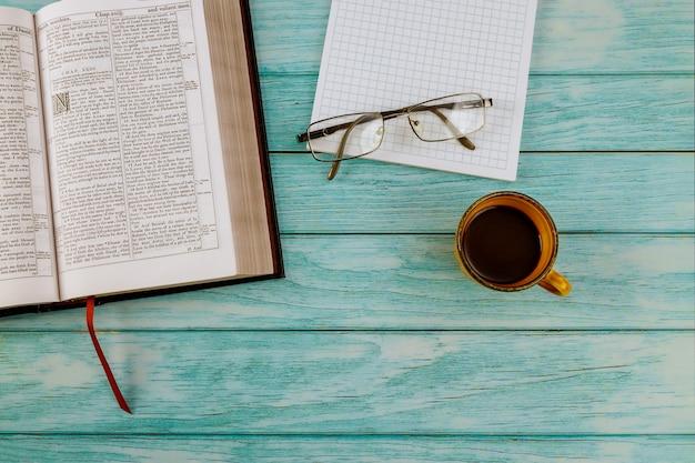 Abra la santa biblia acostada sobre una mesa de madera en una lectura de la taza de café