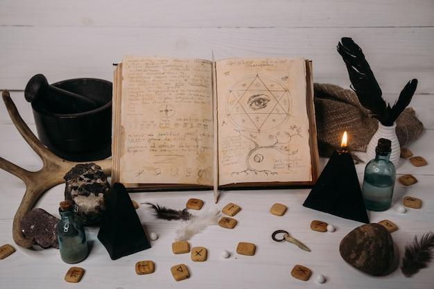 Abra el viejo libro con hechizos mágicos, runas, velas negras y hierbas en la mesa de brujas.