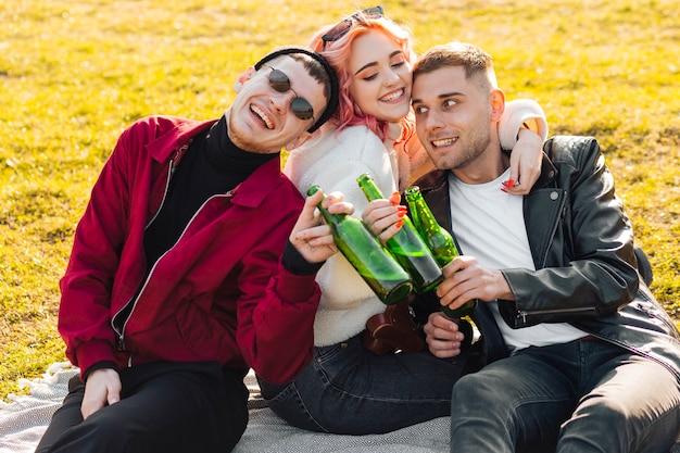 Abrazando amigos felices divirtiéndose juntos en picnic