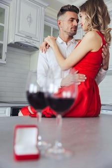 Abrazando hermosa pareja copas con vino y caja con anillo en la mesa