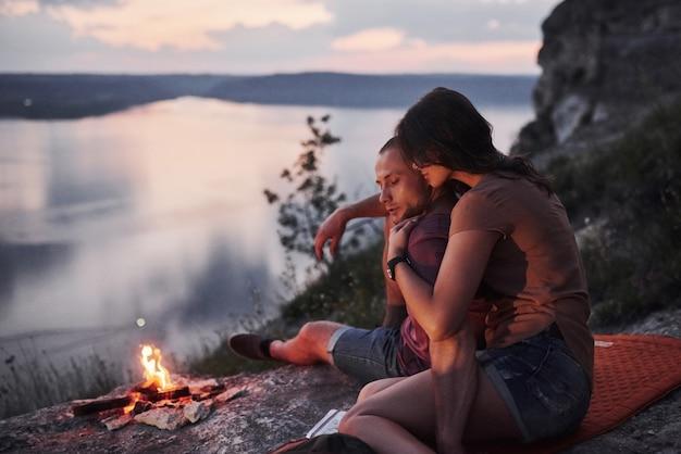 Abrazando pareja con mochila sentado cerca del fuego en la cima de la montaña disfrutando de la vista de la costa de un río o lago.