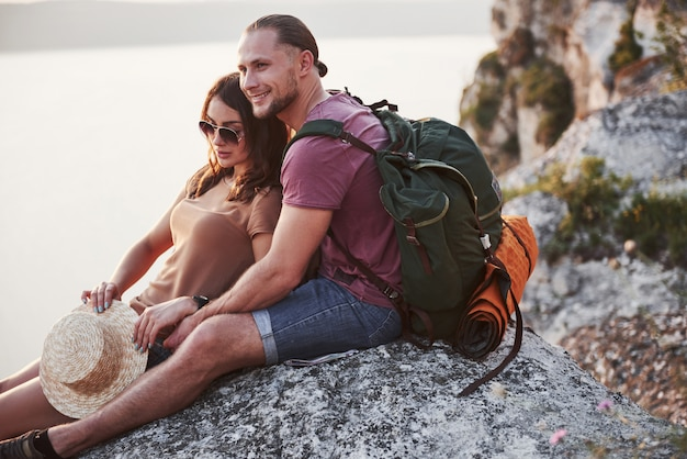 Abrazando pareja con mochila sentado en la cima de la montaña de roca disfrutando de la vista de la costa de un río o lago. viajando por las montañas y la costa, la libertad y el concepto de estilo de vida activo
