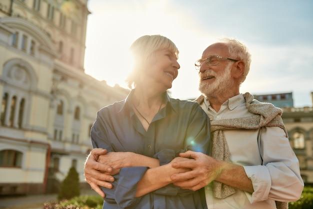 Abrazando el retrato de la feliz y hermosa pareja senior mirando el uno al otro y sonriendo mientras