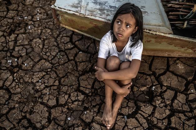 Abrazando sus rodillas y mirando al cielo en tierra seca, hay barcos de pesca, el calentamiento global.