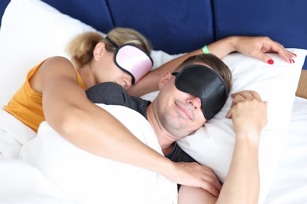 Abrazar, hombre y mujer, con, antifaz para dormir, cama para dormir