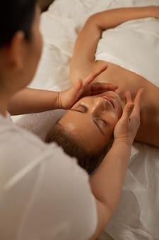 Abrazar suavemente la cara. maestro profesional con movimientos especiales durante el masaje facial en un ambiente relajante.