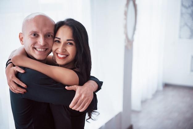 Abrazarse unos a otros y sonriendo. retrato de la feliz pareja en el interior. calvo y morena mujer se encuentra en la sala blanca