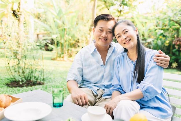 Abrazo asiático de los pares al aire libre en jardín