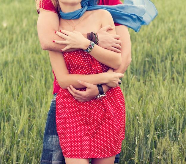 Abrazo de la pareja en un prado Foto gratis