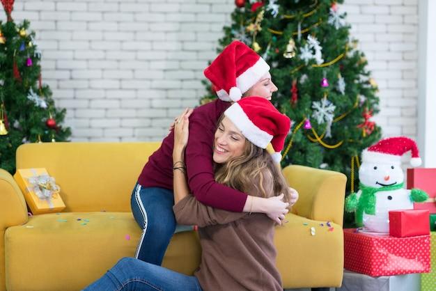 Abrazos, amigas, amigas, novias dan regalo de año nuevo en caja, sonriendo y riendo, junto al árbol de navidad. concepto de hermandad.