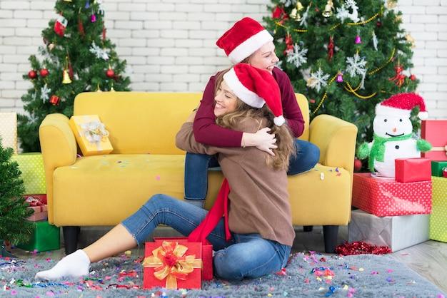 Abrazos, amigas, amigas, novias dan regalo de año nuevo en caja, sonriendo y riendo, junto al árbol de navidad.