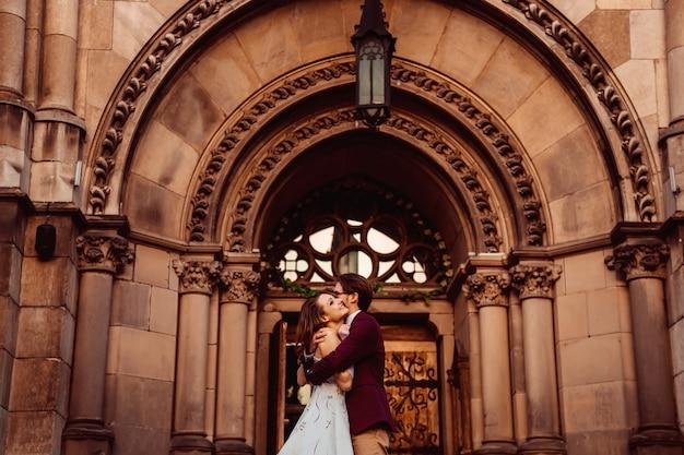 Abrazos apasionados de marido y mujer en traje de novia