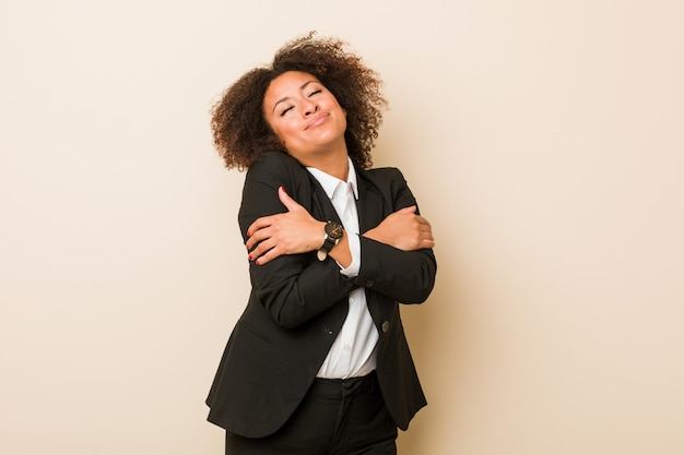 Abrazos de joven mujer afroamericana de negocios, sonriendo despreocupado y feliz.
