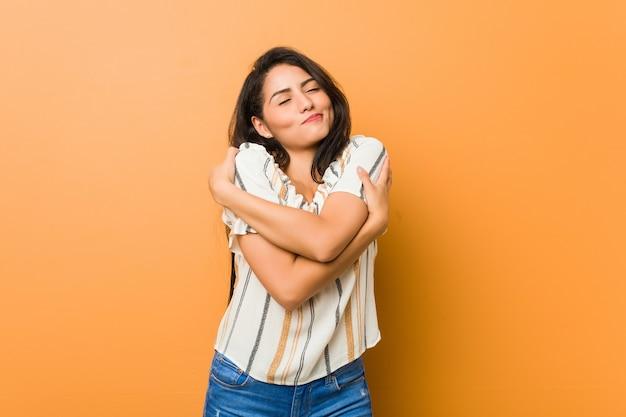Abrazos de mujer joven con curvas, sonriendo despreocupado y feliz.