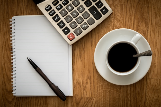 Abre un cuaderno blanco en blanco, un bolígrafo y una taza de café y calculadora