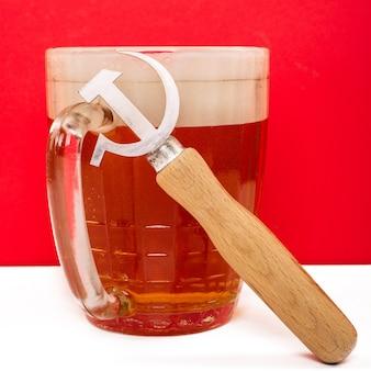 Abridor retro de la era soviética en forma de hoz y martillo junto a una cerveza en rojo