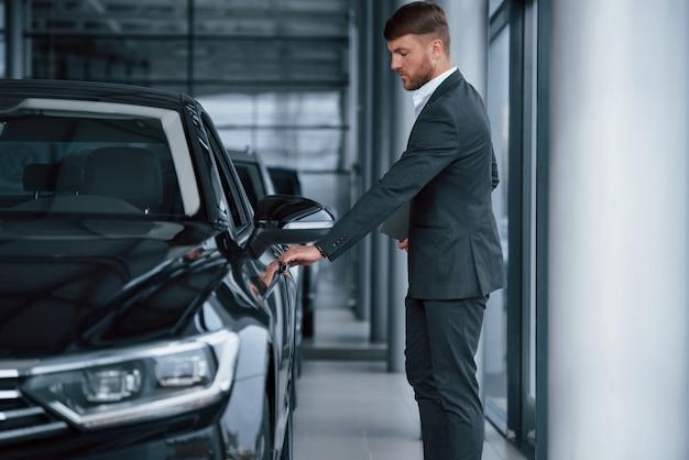 Abriendo la puerta. empresario barbudo con estilo moderno en el salón del automóvil