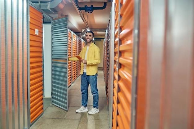 Abriendo puerta. hombre afable barbudo joven optimista en ropa casual con tableta abriendo la puerta del garaje en el trastero