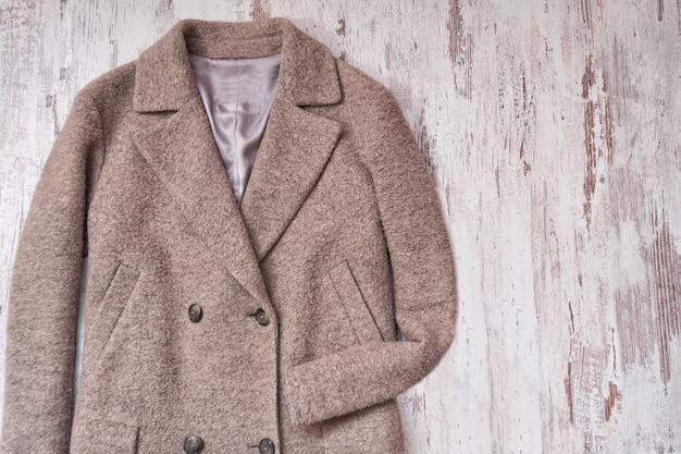 Abrigo de lana marrón, fondo de madera