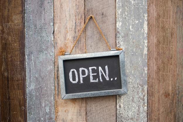 Abrir cartel en la puerta de la tienda de madera
