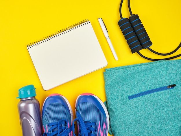 Abrir cuaderno vacío y ropa deportiva femenina para deportes y fitness.