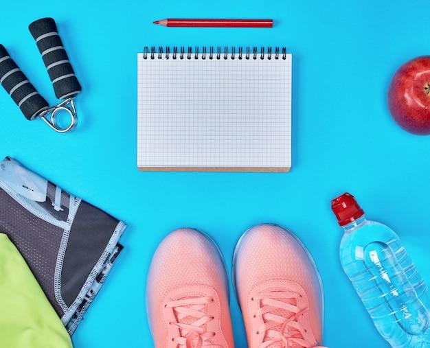 Abrir cuaderno vacío y ropa deportiva femenina para fondo deportivo.