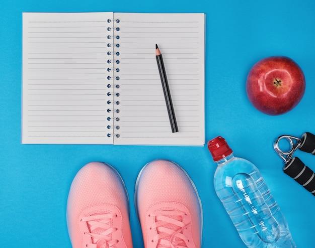 Abrir cuaderno vacío y ropa deportiva para mujer deportiva.