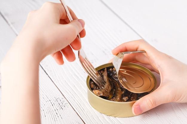 Abrir la lata de pescado y tenedor en la mesa