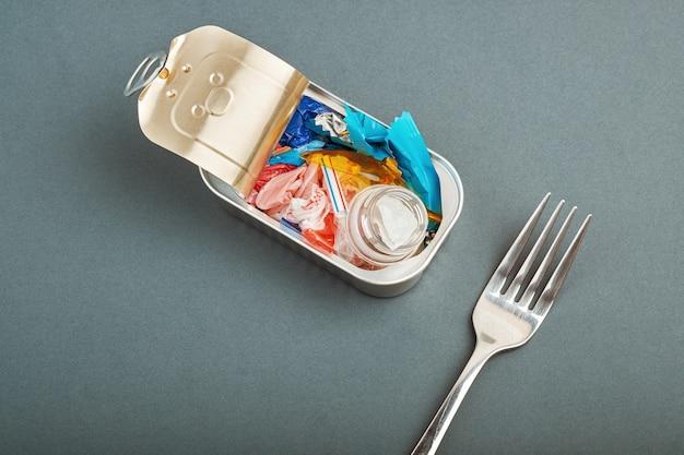 Abrir la lata y el tenedor. residuos de plástico en lugar de peces en el interior. concepto de contaminación plástica del océano
