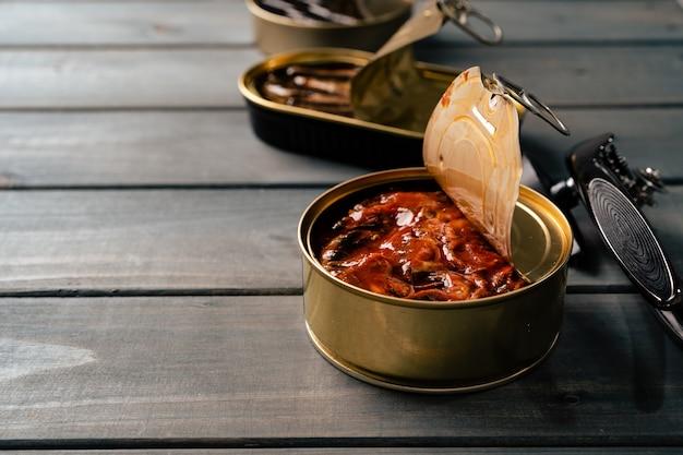 Abrir latas de pescado enlatado en mesa de madera gris
