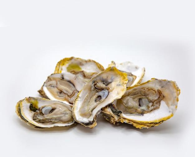 Abrir mariscos frescos de ostras en blanco aislado