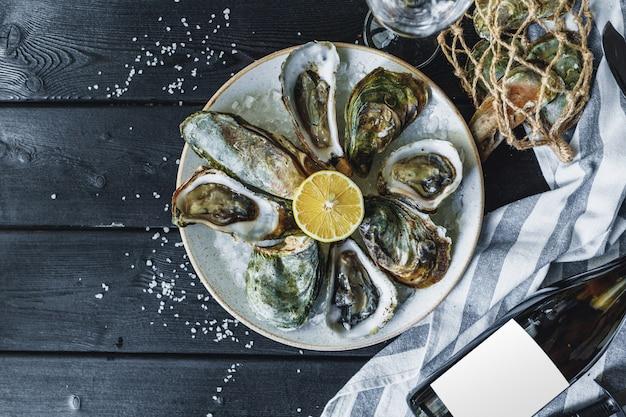 Abrir ostras mojadas en un plato con limón