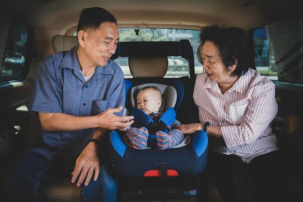 La abuela y el abuelo cuidan de su nieta en un auto, la ayudan y se animan