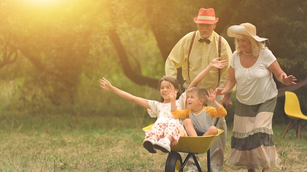 La abuela y el abuelo están empujando a sus nietos en una carretilla de mano.