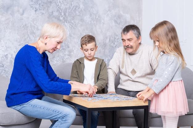 Abuela, abuelo y nieta recogen rompecabezas en la mesa de la sala de estar. la familia pasa tiempo juntos