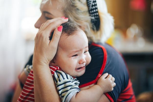 Abuela acunando al bebé infantil gritador que mira la cámara