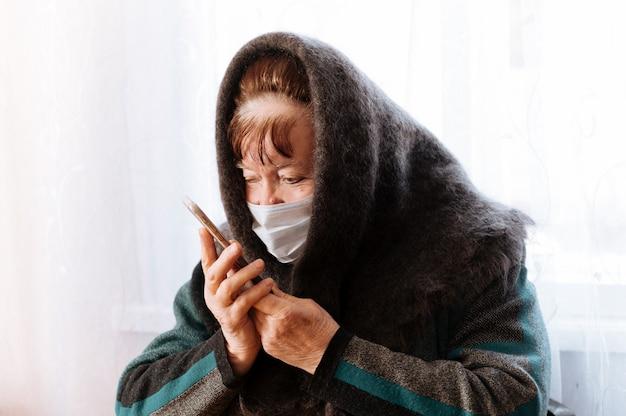 Una abuela anciana con una máscara médica quirúrgica y un pañuelo con un teléfono en las manos.