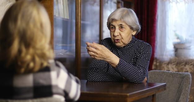 Una abuela con arrugas profundas se comunica con una mujer adulta en casa.