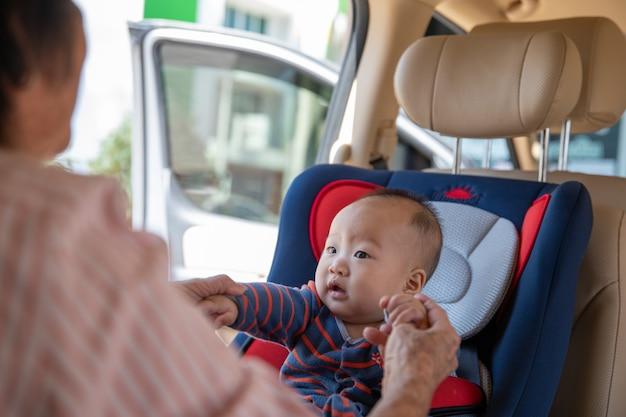 La abuela cuida a su nieta en un auto, la ayuda y se anima