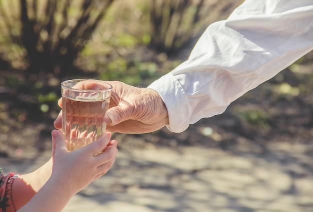 Abuela dando un vaso de agua limpia a un niño. enfoque selectivo