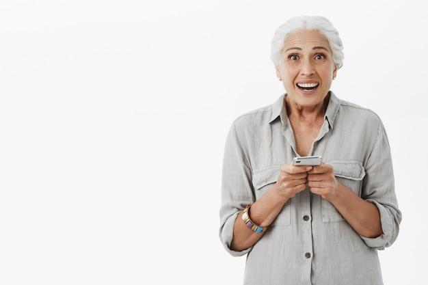 Abuela emocionada y sorprendida sosteniendo el teléfono móvil y sonriendo feliz