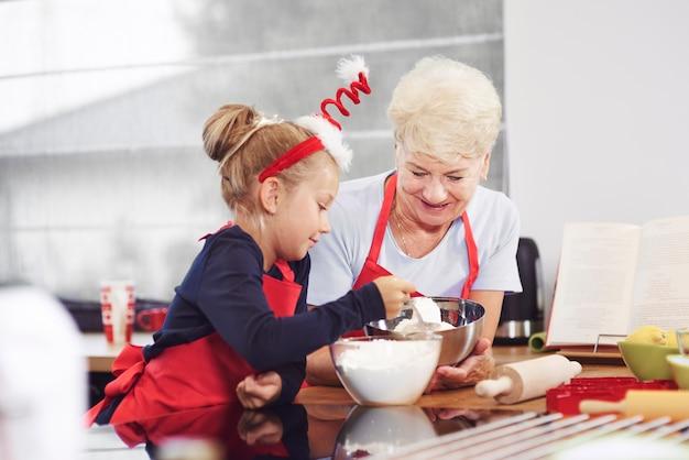 Abuela enseñando a su nieto a hacer un pastel