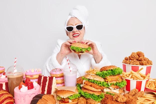 Abuela feliz con gafas de sol sostiene una hamburguesa rodeada de comida rápida