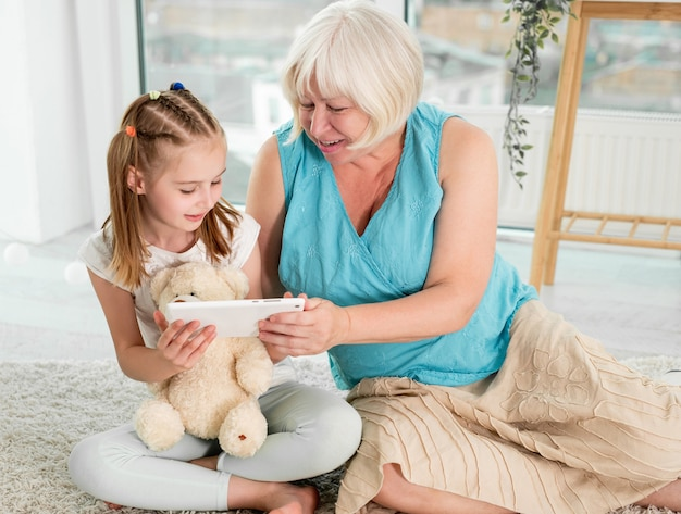 Abuela feliz con nieta pequeña con ubicación de tableta en el piso en la habitación de los niños