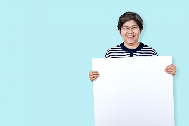 La abuela feliz que sonríe con los dientes blancos, disfruta del momento y que lleva a cabo a un tablero en blanco.