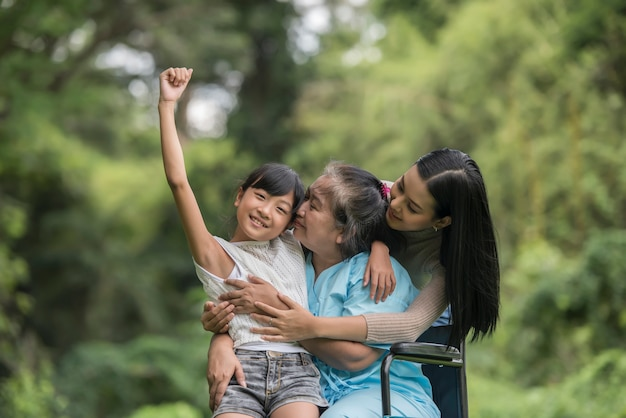 Abuela feliz en silla de ruedas con su hija y su nieto en un parque, feliz vida tiempo feliz.