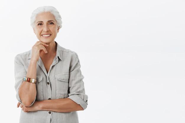 Abuela feliz sonriente mirando sobre fondo blanco.